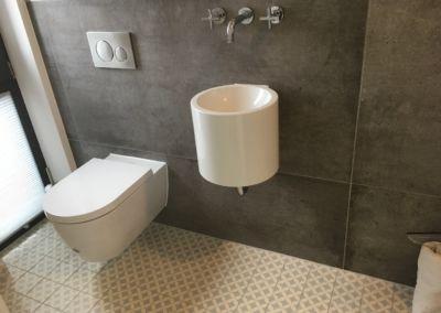 Hänge WC - dunkle große Fliesen und modernes Waschbecken